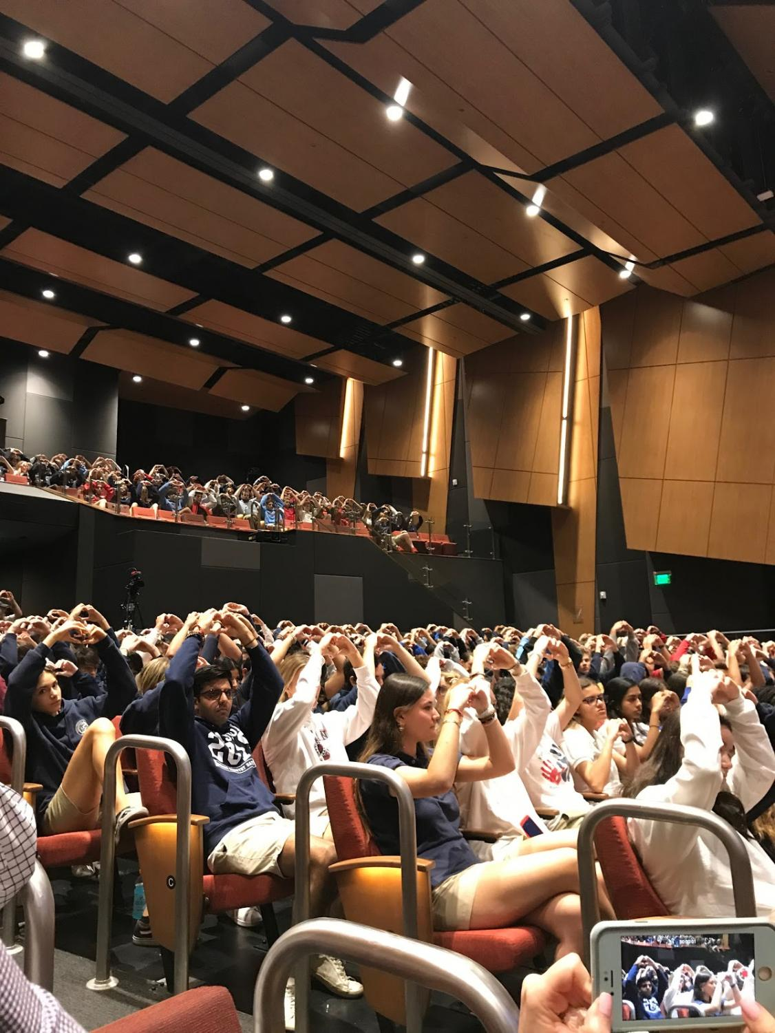 During a MOSS assembly, students raise their arms to give support to the 17 lives lost during the Parkland shooting.